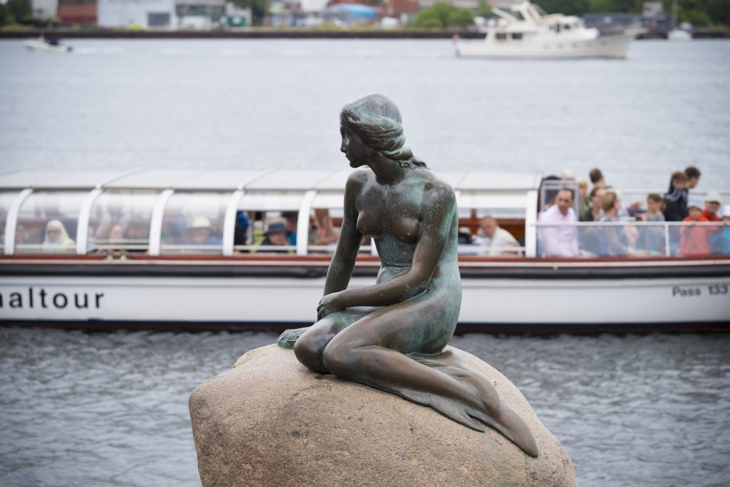 The Little Mermaid is a bronze statue by Edvard Eriksen sitting on a stone in Kopenhagen