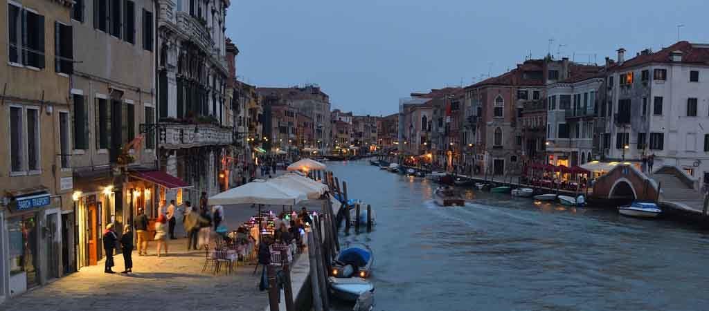 Der Cannaregio Kanal in Venedig am frühen Abend mit beleuchteten Restaurants und Bar