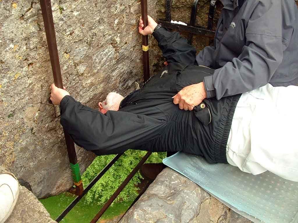 Ein Mann, küsst den Blarney-Stein oben auf dem Schloss