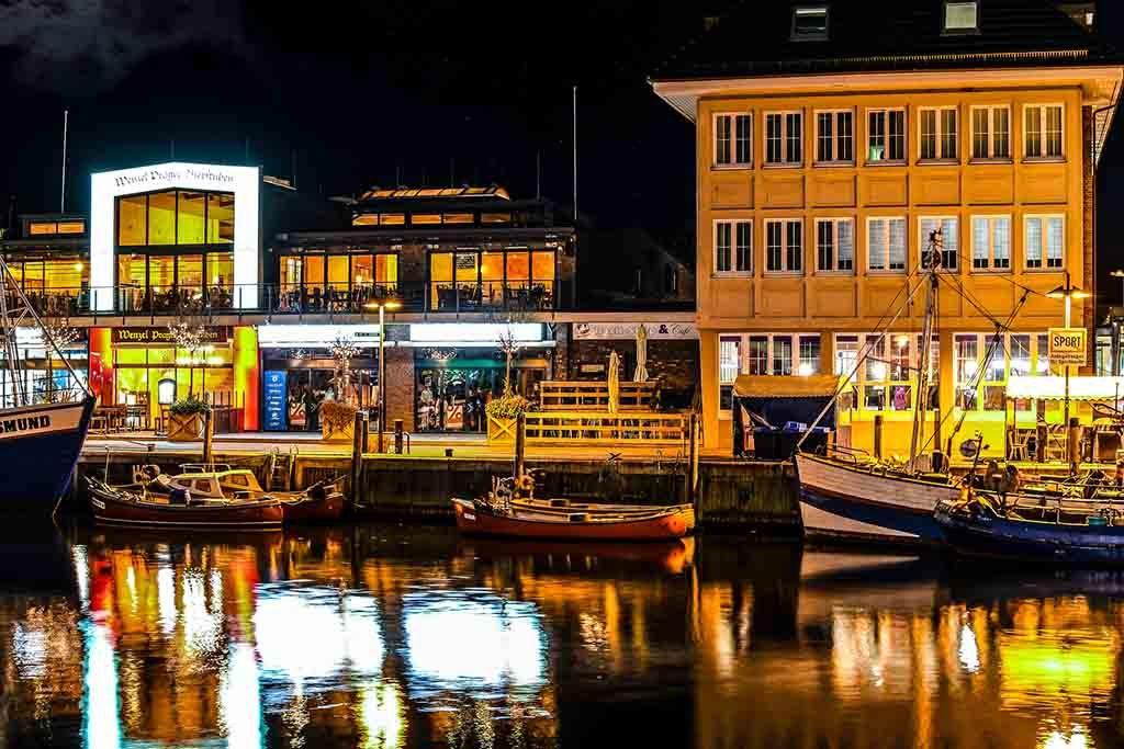 Die abendlich beleuchteten Geschäfte und Cafés am Alten Strom-Kanal in Warnemünde