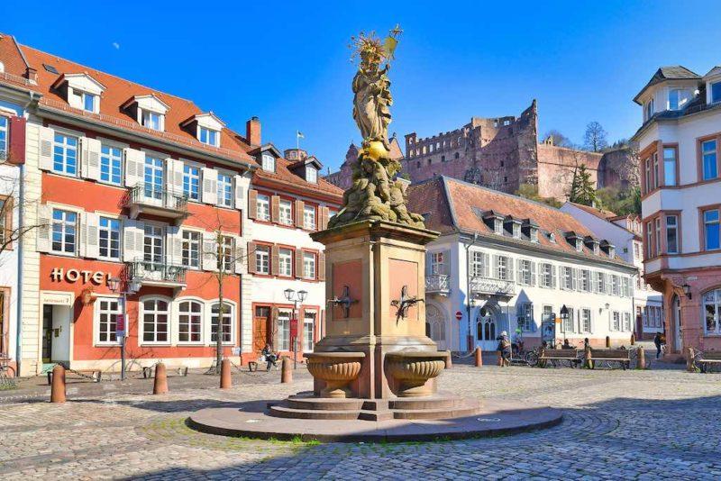 Der Kornmarkt mit der goldenen Madonna-Statue und dem Heidelberger Schloss im Hintergrund